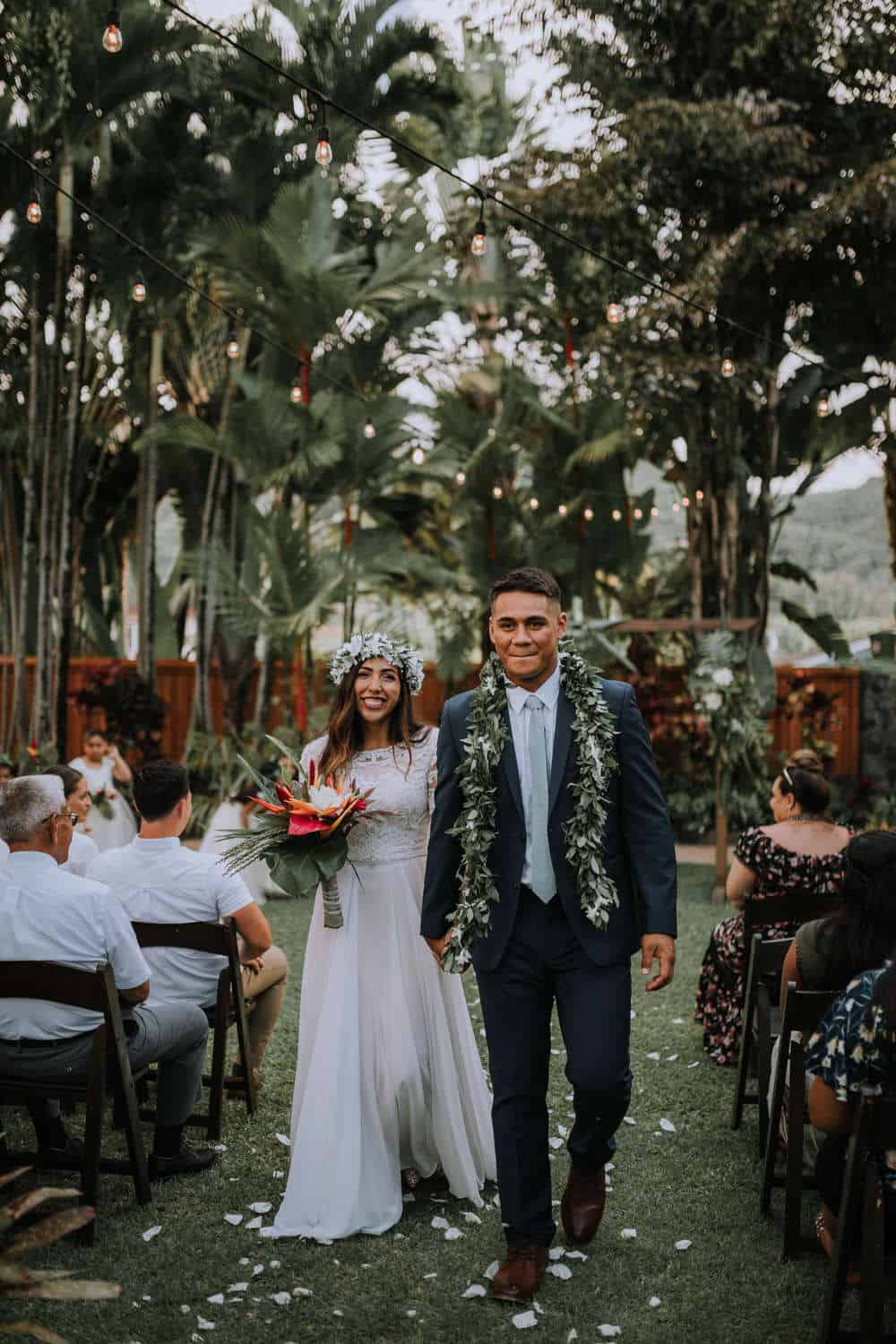 Bride and groom walking down the aisle at the end of their wedding ceremony at Hale Koa Estate in Oahu, Hawaii